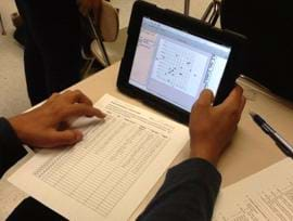 The photo shows a student at a table with a tablet computer showing a graph with a paper listing of data nearby.