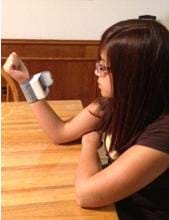 Photo shows a girl looking at a device strapped to her wrist.