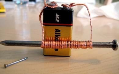A battery connected to a wire that wraps around a nail.