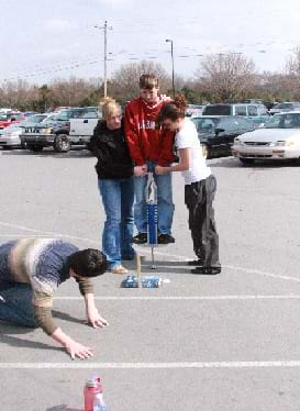 A photograph shows four teens in a parking lot, one on a pogo stick, two helping the boy on the pogo stick and one on his knees, looking at the lower part of the pogo stick.