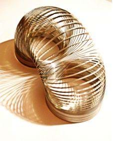 A photograph shows a metal slinky, arched to show its composition.