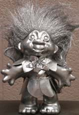 Photo shows a bronzed-looking, standing troll doll with big hair.