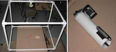 Two photos: (left) A cube shape made with PVC pipes, a round mirror attached to one edge, and a small, orange-haired troll inside. (right) A white tube with a laser pointer and metal box attached to one side.