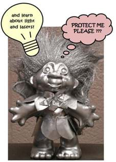 "Photo shows a bronzed troll doll with bubble captions: ""Protect me, please???"" and ""and learn about light and lasers!"""