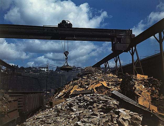 A photograph shows carloads of scrap metal being sorted and moved at the Allegheny Ludlum Steel Corp. in Pennsylvania in the 1940s. An overhead magnet deposits the scrap in a loader that carries it to a furnace to be melted down for re-use.