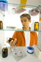 Photo shows young man looking into a medicine cabinet and holding a brown bottle of liquid medicine.