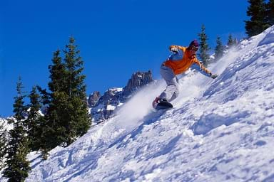 Photo shows a man snowboarding down a steep slope.