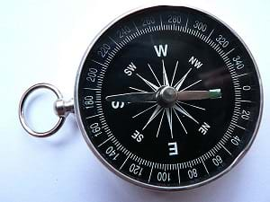 A photograph of a simple magnetic portable compass showing N, S, E, W directions.