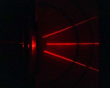 A photograph shows a red laser beam being diffracted into three beams as it passes through a diffraction grating.
