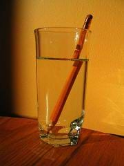 Photo shows a side view of a pencil in a glass of water. The pencil image is refracted at the point where the pencil enters the water.