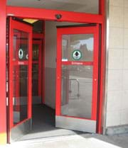 Photo shows double glass doors partially opening inward at store entrance with a sensor positioned above the doorway.