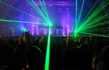 Photo shows beams of green light directed at a darken audience as part of a laser light show from a concert stage.