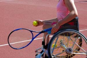 A woman with a physical disability sitting in a wheelchair holding a tennis raquet and tennis ball.