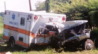 Photo shows an ambulance damaged from a crash. The front cab of the truck is crumpled and torn away from a dented back section.
