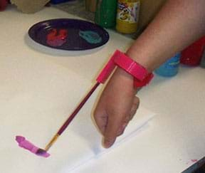 A photograph shows a person's forearm painting on a piece of paper by the use of an assistive device holds a small paintbrush and is attached to her wrist.