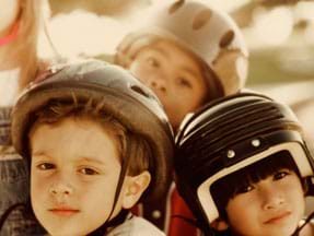 Photo shows three young children wearing helmets.