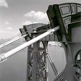 Photo shows close-up of cables at top of a bridge tower.