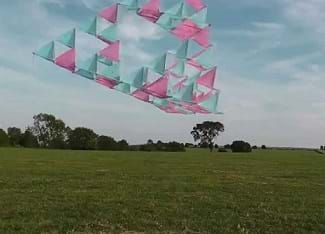 A tetrahedral kite flying in the air.
