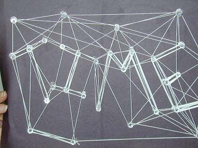 Photo shows a web that spells out TIME made from white string wrapped around push pins poked into a black board.