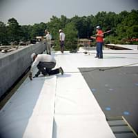 Photo shows four men adhering long white rolls of material to a flat black rooftop.