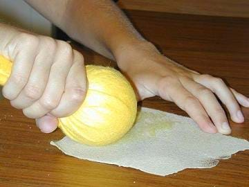 A photograph shows a hand holdin the ends of fabric that is wrapped around a fist-sized ball, while pulling across a piece of sand paper.