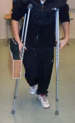 Photo shows a boy using a pair of crutches. Attached to the outer side of one crutch below the hand support is a container—a flat wooden box with the top side open; it contains a notebook.