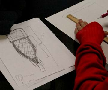 Photo shows a student sketch of a crutch with measurements and an idea for a net-covered frame as a carrying device.