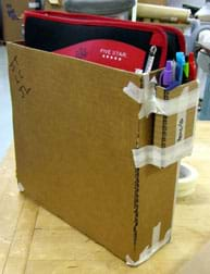 Photo shows an open-topped cardboard box with drafting tape at corner seams; it holds a zipped school notebook/binder. A smaller cardboard box holding three pens is taped to one end of the bigger box.