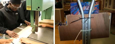 Two photos: A student wearing safety goggles uses a band saw to cut a flat piece of material. An open-topped L-shaped wooden box zip-tied to a crutch below the hand hold. The big part of the box holds a notebook; the small part of the box holds pencils.