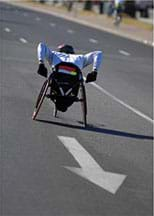 Photo shows a competitor in a sporty wheelchair racing up an asphalt road.