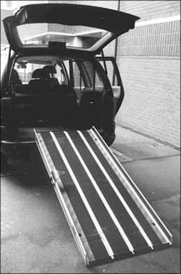 A black and white photo shows a ramp with side edges leaning from the open back of a vehicle to the ground.