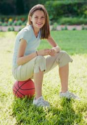 A girl wearing sneakers sits on a basketball.