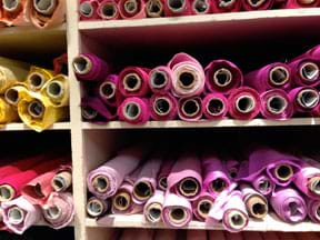 Photograph shows shelves full of cylindrical bolts of fabric.
