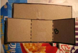 Photo shows the long folded cardboard piece attached to the back of rectangle A cardboard piece.