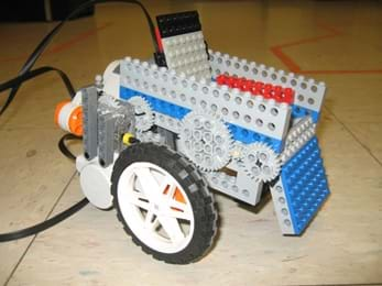 A photograph shows what looks like a chair on wheels with gears and sensors, made from a LEGO robot kit and LEGO pieces.