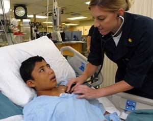 A female nurse checks on a young male patient in a hospital bed by holding a stethoscope on his chest.