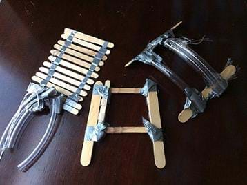 A photograph shows three different hand-device prototypes. All are made of duct tape and regular- and jumbo-sized craft sticks. Two of them also use clear plastic tubing and string.