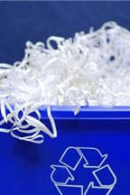 Photograph of a blue recycling bin overflowing with shredded paper.