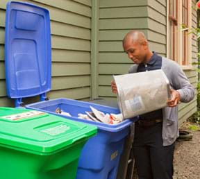 A photograph shows a man emptying a wastebasket of paper into a bigger blue recycling bin full of paper.