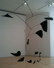 A photograph of a Calder mobile at the SF MOMA - a balance of black wires and random black shapes.