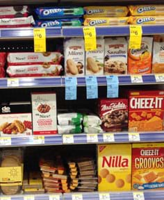 A photograph shows four shelves in a store containing packaged cookies and crackers.