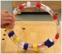 A photograph of a sensory toy shows a ring made of clear plastic tubing covered with scattered stripes of tape in bright colors with moving bells and balls inside the tube.