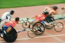 Photo shows a wheelchair race with four competitors in blurred motion.