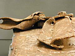 Photo shows two rusty, bent and curved pieces of thick metal.