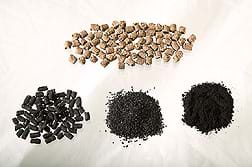 Photo shows four piles: Poultry manure pellets are light brown and short cylinders in shape. Three piles of dark materials are activated carbon in pellet, granular and powdered forms (increasingly fine).
