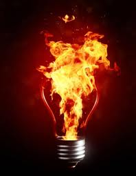 Photo shows flames pouring from a screw-in light bulb.