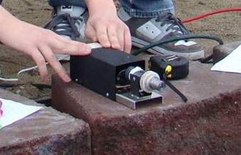 Photo shows a small black box device on a stone block.